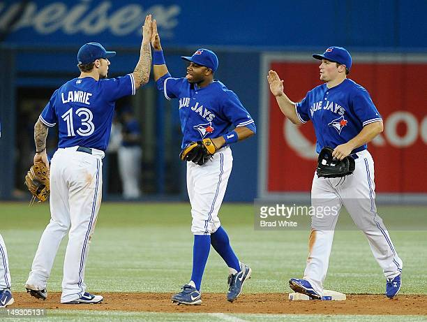 Brett Lawrie, Rajai Davis and Travis Snider of the Toronto Blue Jays celebrate the teams win over the Oakland Athletics during MLB game action July...