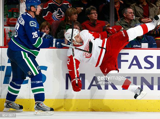 Brett Lebda of the Detroit Red Wings slams into the boards as Mikael Samuelsson of the Vancouver Canucks looks on during their game at General Motors...