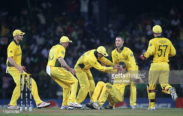 Brett Lee of Australia is assisted to his feet by team mates after taking a catch from his own bowling to dismiss Mohammad Hafeez of Pakistan during...