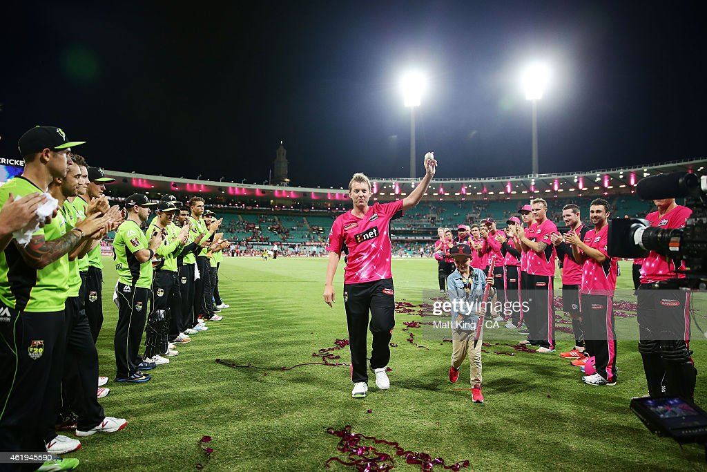 Brett Lee of the Sixers acknowledges the crowd as he walks from the field with his son Preston Lee after his last game at the SCG during the Big Bash League match between the Sydney Sixers and the Sydney Thunder at Sydney Cricket Ground on January 22, 2015 in Sydney, Australia.