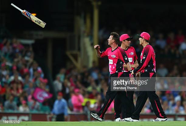 Brett Lee of the Sixers throws Will Sheridan of the Renegades his bat after running him out during the Big Bash League match between the Sydney...