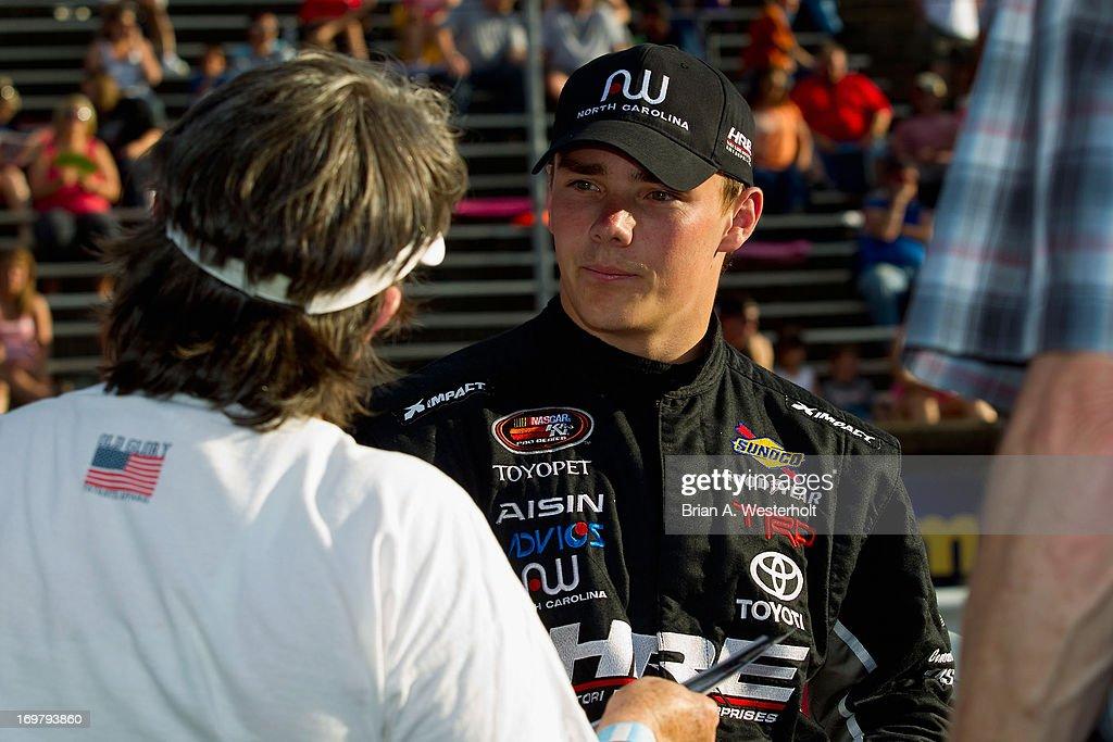Brett Moffitt, driver of the Aisin AW Toyota, signs