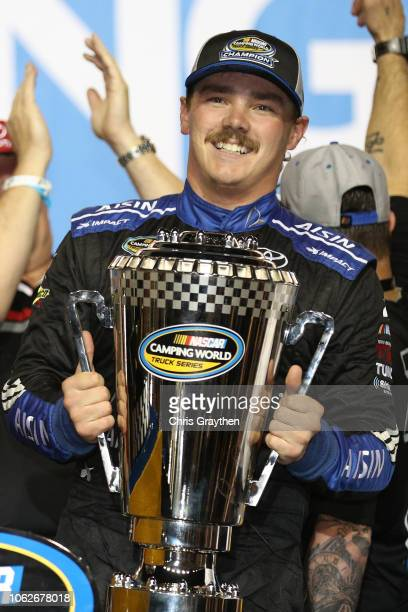Brett Moffitt driver of the AISIN Group Toyota celebrates in victory lane with the trophy after winning the NASCAR Camping World Truck Series Ford...