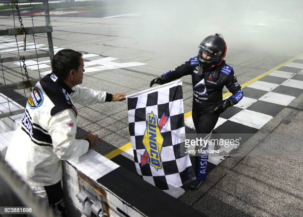 Brett Moffitt driver of the AISIN Toyota takes the checkered flag from a NASCAR official after winning the NASCAR Camping World Truck Series Active...