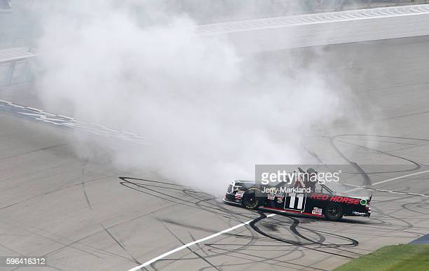 Brett Moffitt driver of the Red Horse Racing Toyota celebrates with a burnout after winning the NASCAR Camping World Truck Series Careers for...
