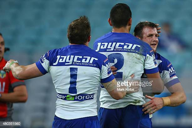 Brett Morris, Curtis Rona and Josh Morris of the Bulldogs celebrate after Josh Morris scored a try during the round 18 NRL match between the...