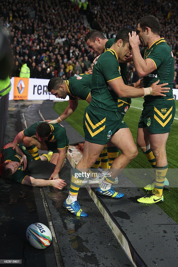 Brett Morris (L) of Australia lies injured after crashing into the advertising hordings having scored a try during the Rugby League World Cup Final between Australia and New Zealand at Old Trafford on November 30, 2013 in Manchester, England.
