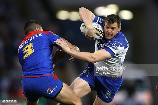 Brett Morris of the Bulldogs is tackled during the round 25 NRL match between the Newcastle Knights and the Canterbury Bulldogs at Hunter Stadium on...