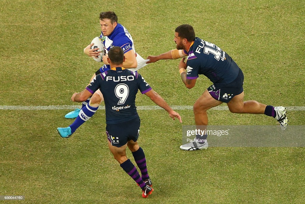 Brett Morris of the Bulldogs looks to break from a tackle by Kenneath Bromwich of the Storm during the round one NRL match between the Canterbury Bulldogs and the Melbourne Storm at Optus Stadium on March 10, 2018 in Perth, Australia.