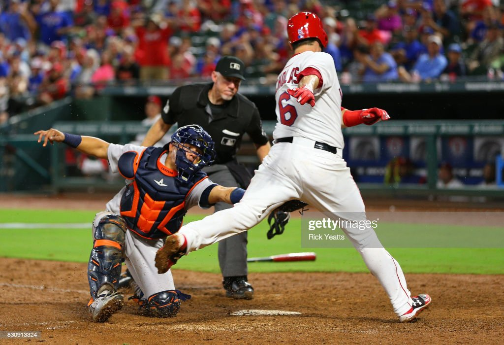 Brett Nicholas #6 of the Texas Rangers is tagged out in the sixth inning by Juan Centeno #30 of the Houston Astros at Globe Life Park in Arlington on August 12, 2017 in Arlington, Texas.