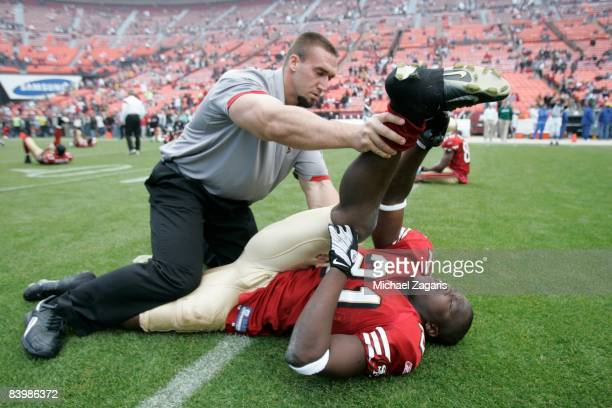 Brett Nichols stretches Frank Gore of the San Francisco 49ers before an NFL football game against the New York Jets at Candlestick Park on December...