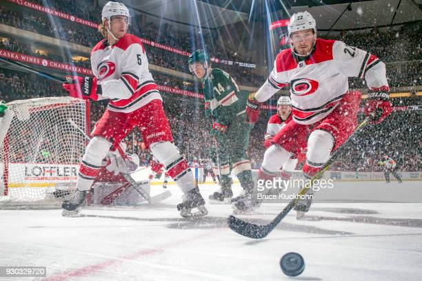 Brett Pesce and Noah Hanifin of the Carolina Hurricanes skate to the puck against the Minnesota Wild during the game at the Xcel Energy Center on...
