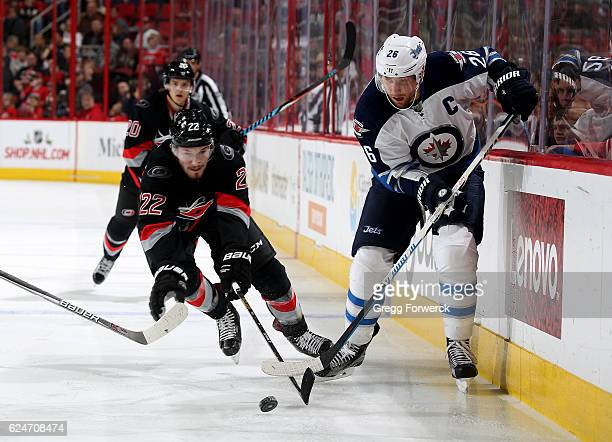Brett Pesce of the Carolina Hurricanes and Blake Wheeler of the Winnipeg Jets battle to control the puck along the boards during an NHL game on...