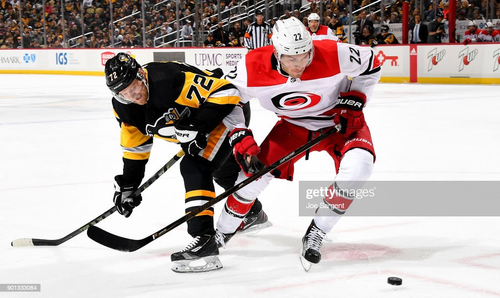 Brett Pesce #22 of the Carolina Hurricanes and Patric Hornqvist #72 of the Pittsburgh Penguins battle for the puck at PPG Paints Arena on January 4, 2018 in Pittsburgh, Pennsylvania.
