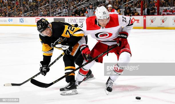 Brett Pesce of the Carolina Hurricanes and Patric Hornqvist of the Pittsburgh Penguins battle for the puck at PPG Paints Arena on January 4 2018 in...