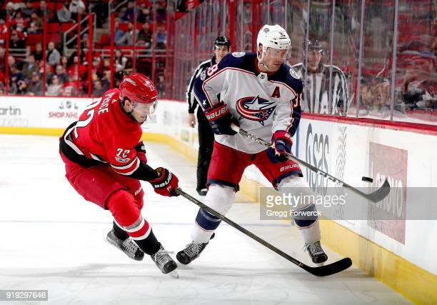 Brett Pesce of the Carolina Hurricanes battles along the boards for a loose puck against Boone Jenner of the Columbus Blue Jackets during an NHL game...