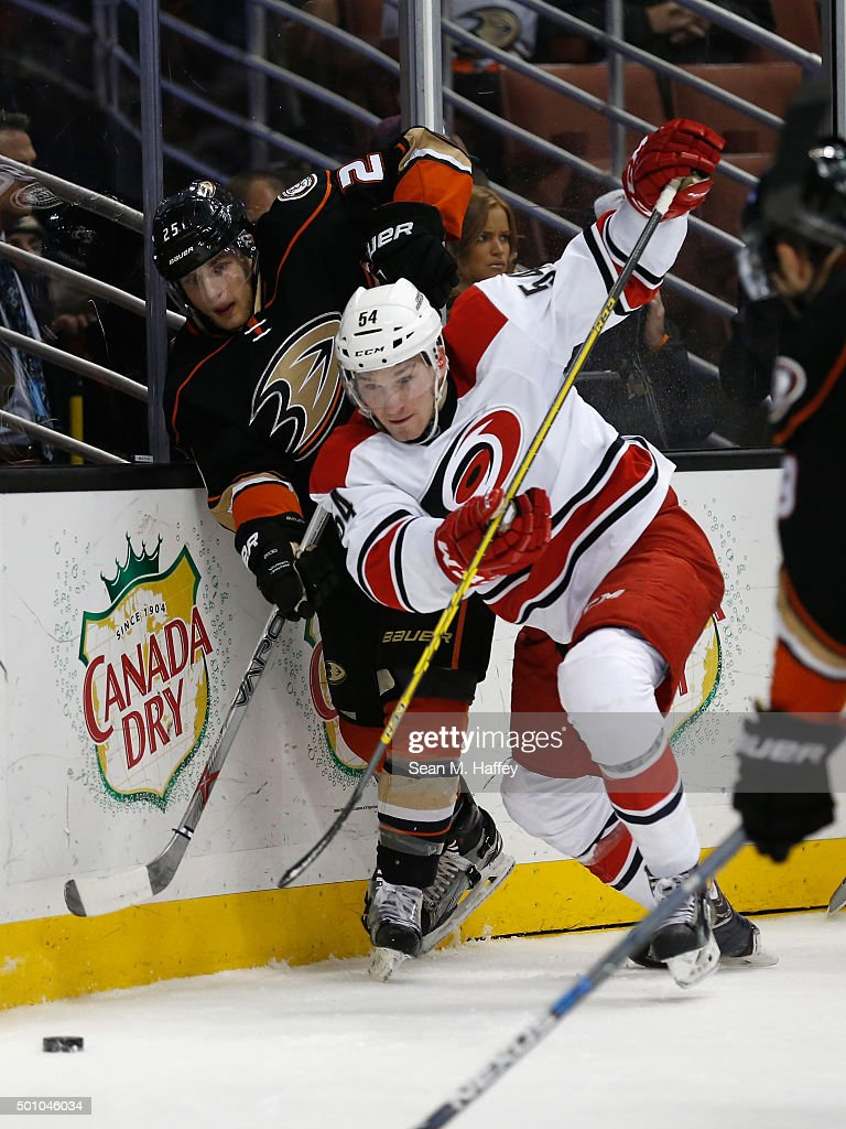 Brett Pesce #54 of the Carolina Hurricanes battles Mike Santorelli #25 of the Anaheim Ducks for a loose puck during the third period of a game at Honda Center on December 11, 2015 in Anaheim, California.