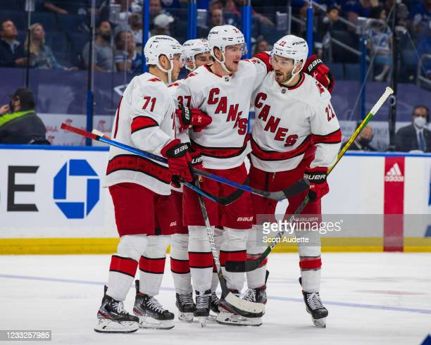 Brett Pesce of the Carolina Hurricanes celebrates a goal with teammates Jesper Fast and Andrei Svechnikov against the Tampa Bay Lightning during the...