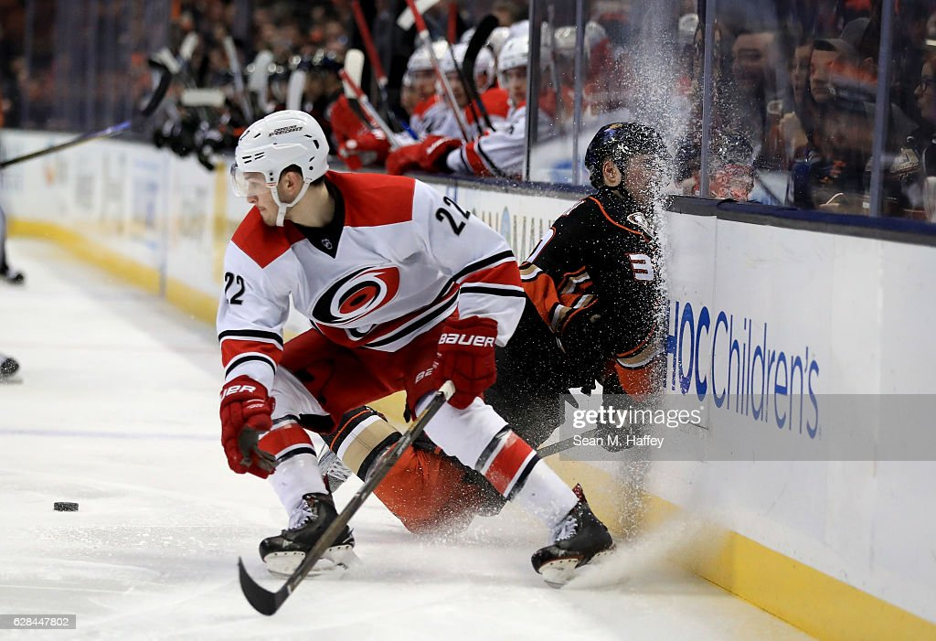 Brett Pesce #22 of the Carolina Hurricanes checks Nick Ritchie #37 of the Anaheim Ducks into the boards during the third period of a game at Honda Center on December 7, 2016 in Anaheim, California.