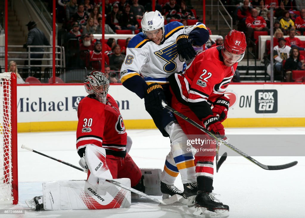 Brett Pesce #22 of the Carolina Hurricanes defends Magnus Paajarvi #56 of the St. Louis Blues as Cam Ward #30 reacts to a shot during an NHL game on October 27, 2017 at PNC Arena in Raleigh, North Carolina.