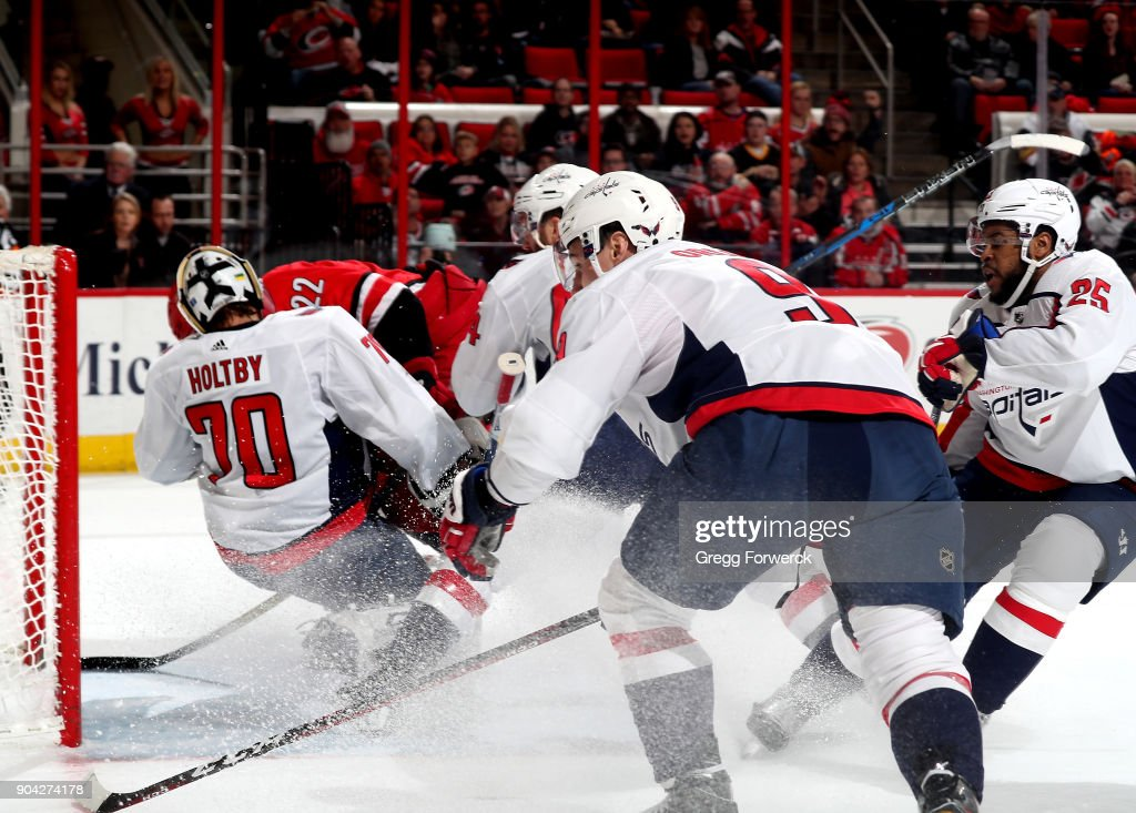 Brett Pesce #22 of the Carolina Hurricanes is checked by Brooks Orpik #44 of the Washington Capitals forcing a collision with teammate Braden Holtby #70 who is knocked into the goal during an NHL game on January 2, 2018 at PNC Arena in Raleigh, North Carolina.