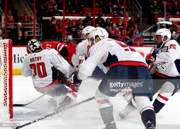 Brett Pesce of the Carolina Hurricanes is checked by Brooks Orpik of the Washington Capitals forcing a collision with teammate Braden Holtby who is...