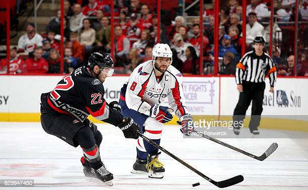 Brett Pesce of the Carolina Hurricanes looks to maintain control of a loose puck as Alexander Ovechkin of the Washington Capitals battles during an...