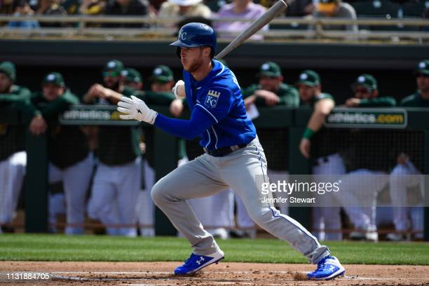 Brett Phillips of the Kansas City Royals hits an RBI single in the first inning against the Oakland Athletics at HoHoKam Stadium on February 24 2019...