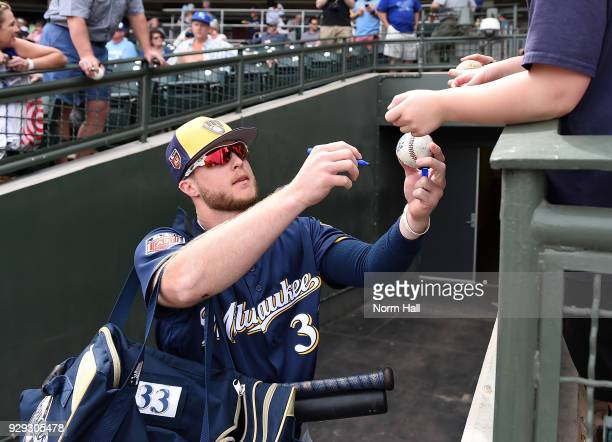 Brett Phillips of the Milwaukee Brewers signs autographs prior to a spring training game against the Kansas City Royals at Surprise Stadium on March...