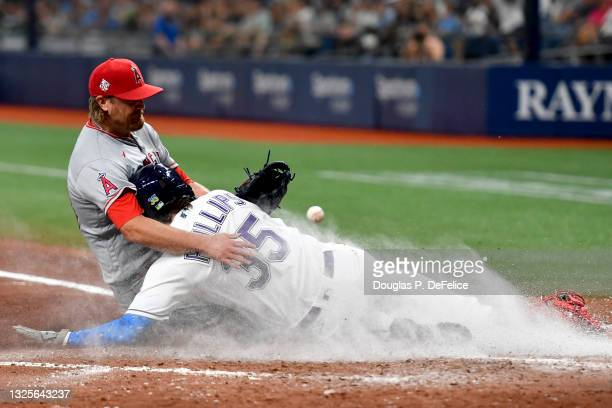 Brett Phillips of the Tampa Bay Rays steals home plate safely on a wild pitch as Alex Cobb of the Los Angeles Angels covers the play during the...