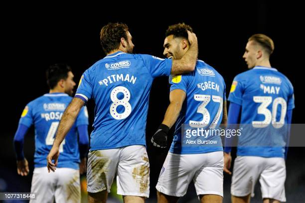 Brett Pitman of Portsmouth celebrates with teammate Andre Green after scoring his team's first goal during the Checkatrade Trophy match between...
