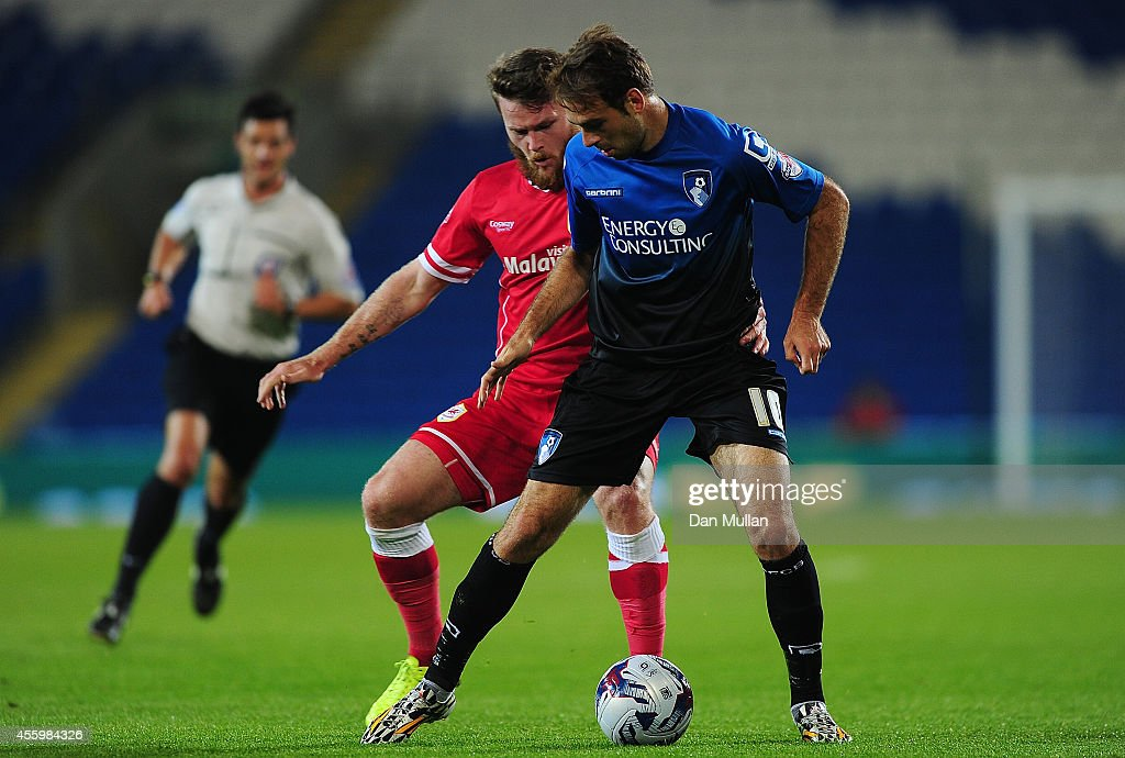Brett Pitmn of Bournemouth holds off Aron Gunnarsson of Cardiff City during the Capital One Cup third round match between Cardiff City and Bournemouth at Cardiff City Stadium on September 23, 2014 in Cardiff, Wales.