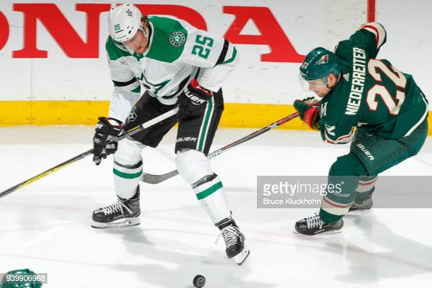 Brett Ritchie of the Dallas Stars and Nino Niederreiter of the Minnesota Wild battle for the puck during the game at the Xcel Energy Center on March...