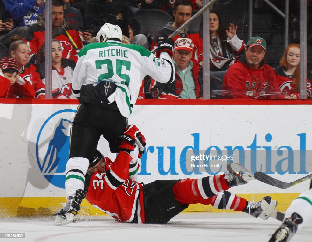 Brett Ritchie #25 of the Dallas Stars checks Steven Santini #34 of the New Jersey Devils during the third period at the Prudential Center on March 26, 2017 in Newark, New Jersey. The Stars defeated the Devils 2-1 in overtime.
