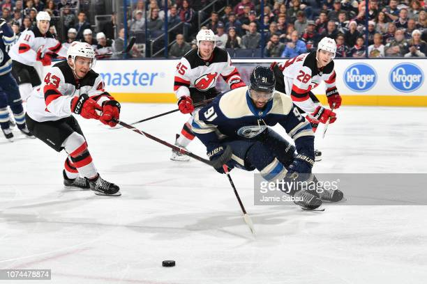 Brett Seney of the New Jersey Devils and Anthony Duclair of the Columbus Blue Jackets skate after a loose puck during the third period of a game on...