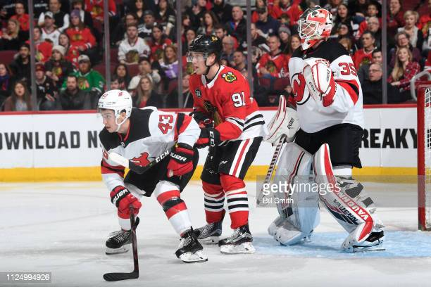 Brett Seney of the New Jersey Devils and Drake Caggiula of the Chicago Blackhawks wait in position in front of goalie Cory Schneider in the third...