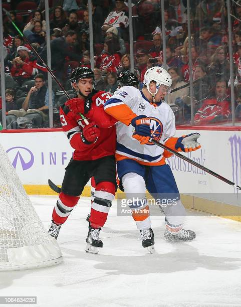 Brett Seney of the New Jersey Devils and Ross Johnston of the New York Islanders battle for position during the game at Prudential Center on November...