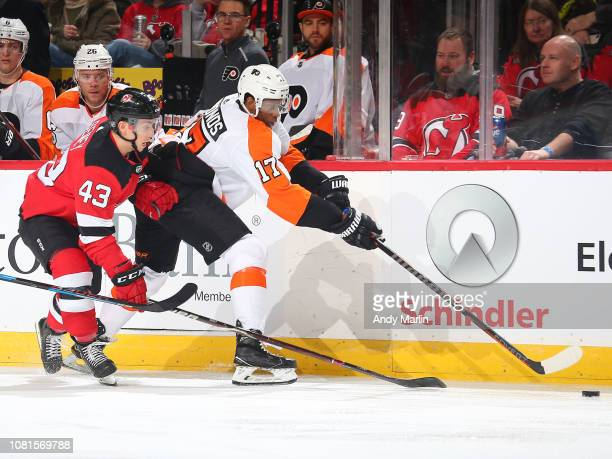 Brett Seney of the New Jersey Devils attempts to gain possession of the puck from Wayne Simmonds of the Philadelphia Flyers during the third period...