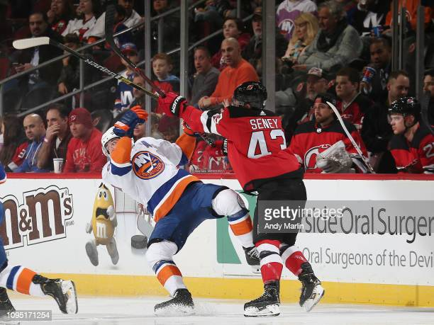 Brett Seney of the New Jersey Devils checks Cal Clutterbuck of the New York Islanders during the first period at the Prudential Center on February 7...