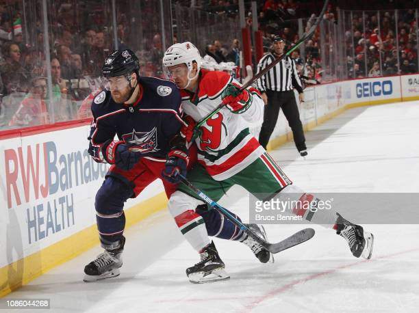 Brett Seney of the New Jersey Devils pushes David Savard of the Columbus Blue Jackets towards the boards during the first period t the Prudential...