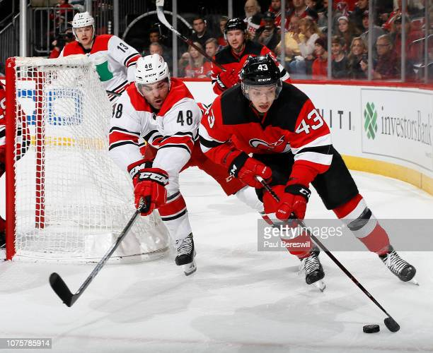 Brett Seney of the New Jersey Devils skates past Jordan Martinook of the Carolina Hurricanesin the first period of an NHL hockey game at the...