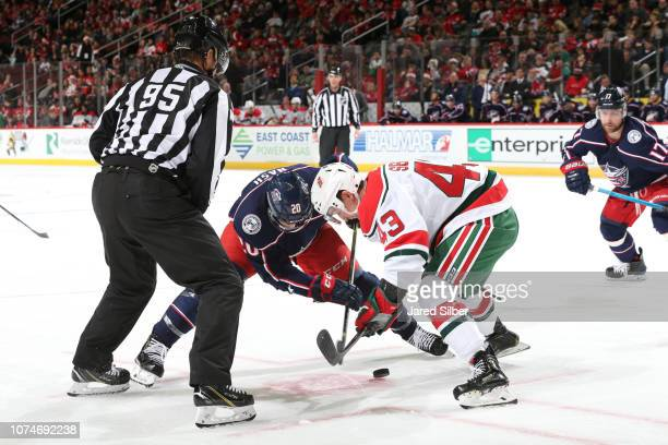 Brett Seney of the New Jersey Devils takes a face off against Riley Nash of the Columbus Blue Jackets at Prudential Center on December 23 2018 in...