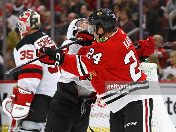 Brett Seney of the New Jersey Devils takes a stick to the neck from Dominik Kahun of the Chicago Blackhawks at the United Center on February 14 2019...