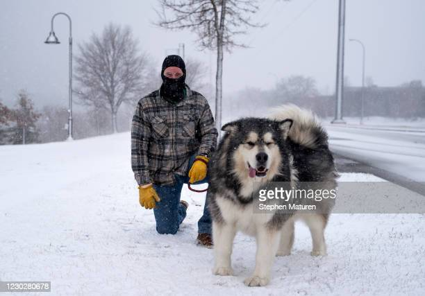 Brett Sorenson walks his dog, an Alaskan Malamute named Pax, as snow falls along the Mississippi River on December 23, 2020 in Minneapolis,...
