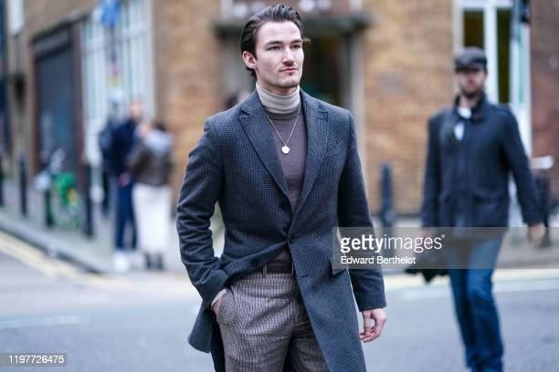 Brett Staniland wears a turtleneck pullover a gray long jacket pants a necklace a belt during London Fashion Week Men's January 2020 on January 05...