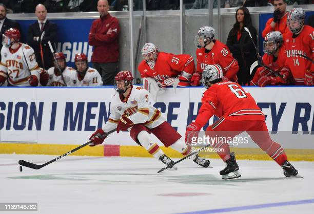 Brett Stapley of the Denver Pioneers skates with the puck against Tommy Parran of the Ohio State Buckeyes during an NCAA Division I Men's Ice Hockey...