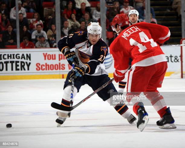 Brett Sterling of the Atlanta Thrashers tries to skate by the defense of Derek Meech of the Detroit Red Wings during a NHL game on October 24 2008 at...