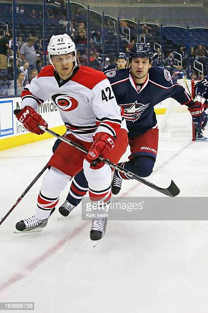 Brett Sutter of the Carolina Hurricanes and Fedor Tyutin of the Columbus Blue Jackets battle for control of a loose puck on September 26, 2013 in a...