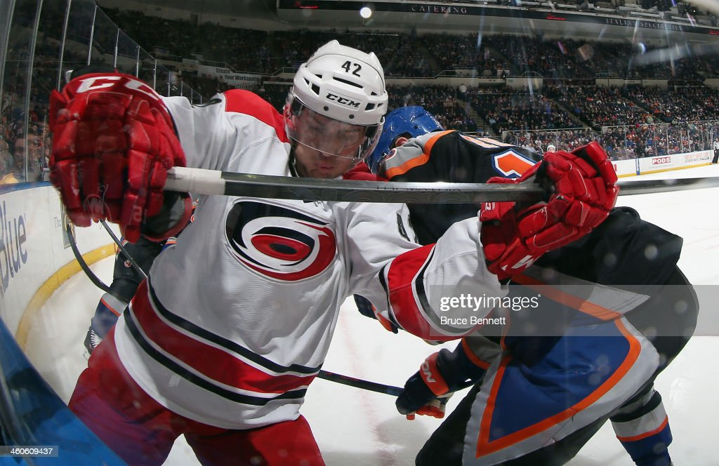 Brett Sutter #42 of the Carolina Hurricanes battles with Peter Regin #16 of the New York Islanders along the boards during the second period at the Nassau Veterans Memorial Coliseum on January 4, 2014 in Uniondale, New York.