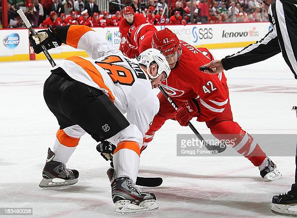 Brett Sutter of the Carolina Hurricanes faces off against Adam Hall of the Philadelphia Flyers during an NHL game on October 6, 2013 at PNC Arena in...